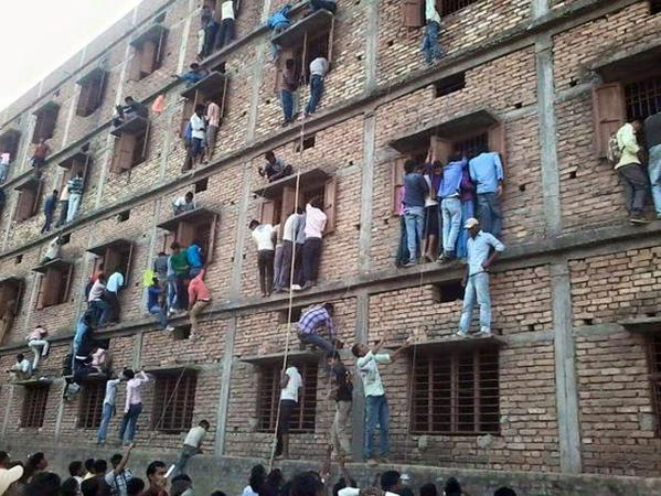 Parents in the state of Bihar climb the walls of a school building to pass exam answers to children inside.