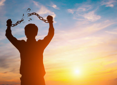Silhouette image of a man with broken chains in sunset, symbolizing a gap year