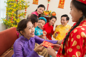 Senior Vietnamese woman giving her granddaughter a red envelope for Tet